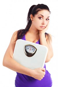 photo of a young woman holding a scale | GA Dermatology Center