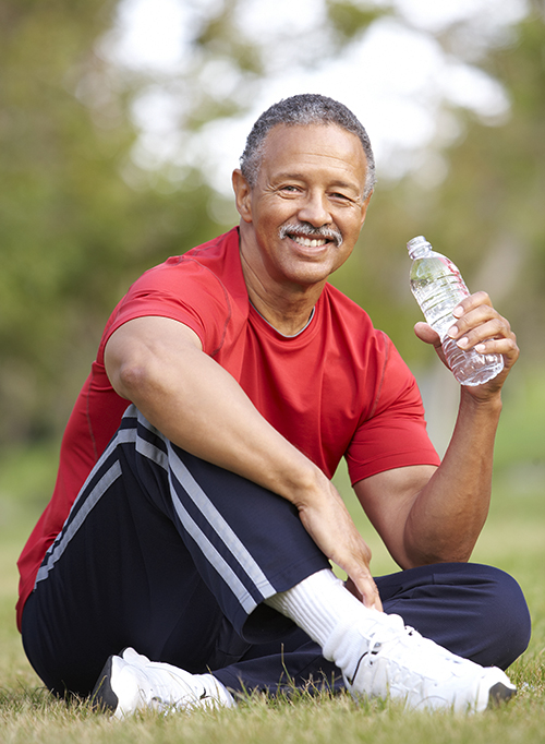 photo of a senior man relaxing after exercise and drinking water