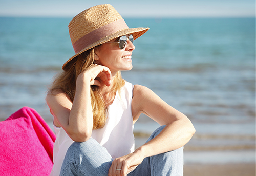 Portait of happy mature woman wearing straw hat and sunglasses while at the beach on a sunny day.