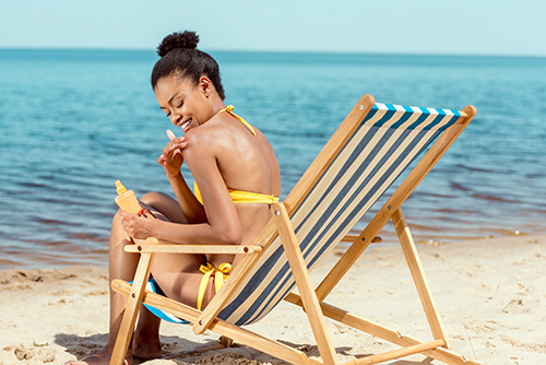 african american woman applying sunscreen lotion on skin while sitting on deck chair on sandy beach